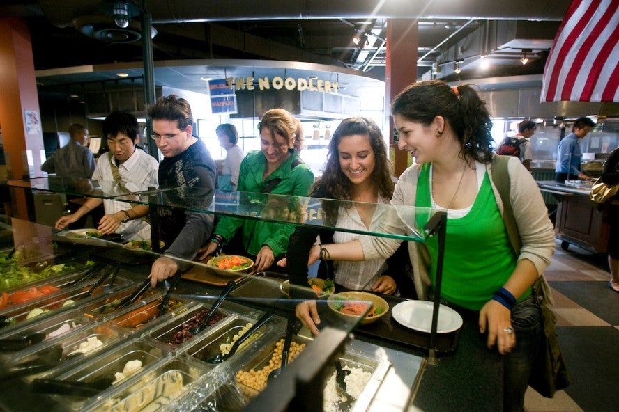 Various students work their way through the dining hall line with their trays choosing from Tufts University's food choices.