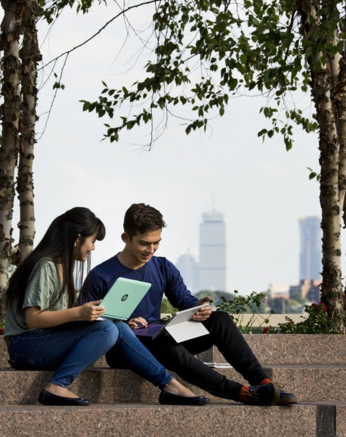 Two student collaborate while sitting on library roof