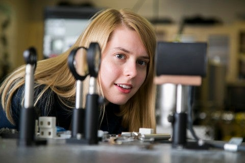 Female engineering student from Tufts University bends down looking at instruments on lab bench