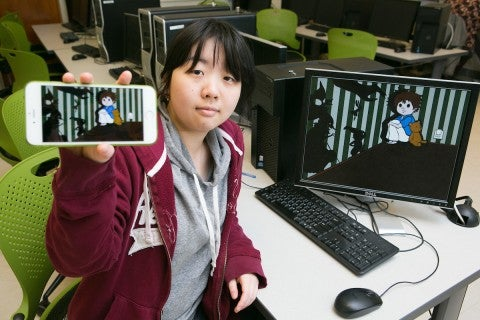 Female engineering student from Tufts University sitting in front of .a computer and showing a game on her phone to the camera