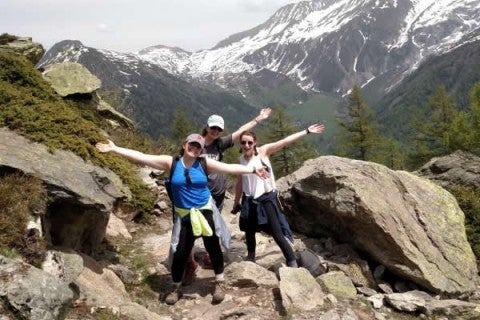 Three college students on a hike, posing in front of a large snowcapped mountain in Tufts Talloires France campus