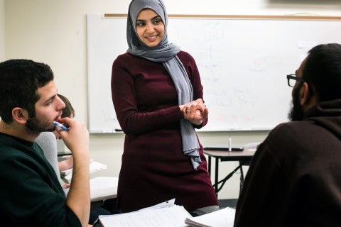 An instructor teaches Arabic to two students in a classroom